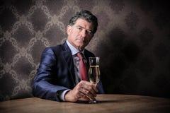 Affärsman med ett exponeringsglas av vin Arkivbild