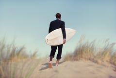 Affärsman med surfingbrädan som går till stranden Royaltyfri Fotografi