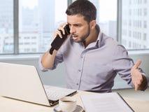 Affärsman på kontoret framme av den talande rubbningen för skyskrapafönstersikt på telefonen som arbetar med datoren Royaltyfria Foton
