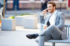Affärsman On Park Bench med kaffe genom att använda mobiltelefonen Royaltyfri Bild