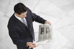 Affärsman Reading Newspaper Indoors Arkivbild
