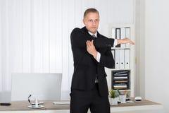 Affärsman som i regeringsställning sträcker Arkivbilder