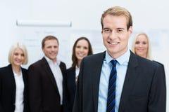 Affärsman som ler med ett lag bak honom Arkivfoton