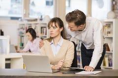 Affärsman som retar hans kollega på arbete Arkivfoto