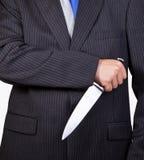Affärsman som rymmer en kniv Arkivbild