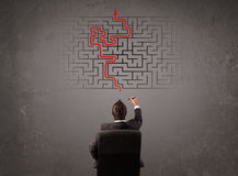 Affärsman som ser en labyrint och utfarten Arkivbild