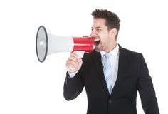 Affärsman som skriker in i megafonen Arkivfoton