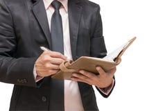 Affärsman som skriver anmärkningsboken Arkivfoto