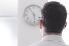 Affärsman som stirrar på klockan Arkivbild