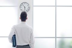 Affärsman som stirrar på klockan Arkivfoto