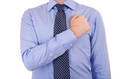 Affärsman som tar ed med näven över hjärta. Fotografering för Bildbyråer