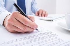 Affärsman som undertecknar ett dokument. Royaltyfri Fotografi