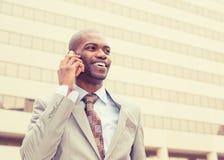 Affärsman som utanför talar på mobiltelefonen Arkivbild