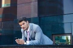 Affärsman som utomhus använder smartphonen Fotografering för Bildbyråer