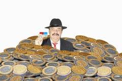 Affärsman under vikten av mynt Arkivfoton