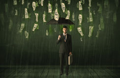 Affärsmananseende med paraplyet i begrepp för regn för dollarräkning Arkivbild