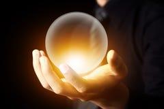 Affärsmanhand som rymmer en Crystal Ball Arkivbilder