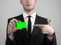 Affärsmannen i en svart dräkt och smoking som rymmer ett kort, en hand som rymmer ett kort, det gröna kortet, kort sätts in, den  Royaltyfria Bilder