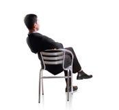 Affärsmannen sitter ner i enkel stol Arkivbild