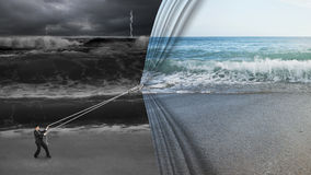 Affärsmannen som drar den öppna gardinen för det lugna havet, täckte mörka stormiga oc Fotografering för Bildbyråer