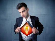 Affärsmannen som river sönder av skjortan och ljus kula för idé, syns Royaltyfri Fotografi