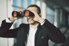 AffärsmanUsing Binoculars In kontor Royaltyfria Bilder