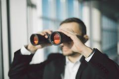 AffärsmanUsing Binoculars In kontor Royaltyfri Fotografi