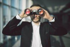AffärsmanUsing Binoculars In kontor Royaltyfri Foto
