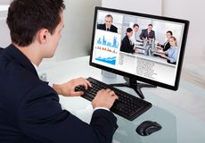 Affärsmanvideoconferencing med laget i regeringsställning Royaltyfria Bilder