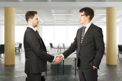 Affärspartners skakar deras händer i modernt öppet utrymmekontor Royaltyfri Fotografi