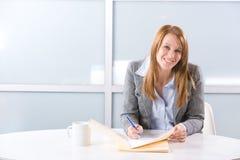 affärsskrivbordet bemärker kvinnawriting Royaltyfri Fotografi