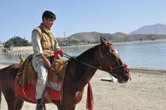 Afgański jeździec na Horseback jazdie na jeziornym brzeg zdjęcia stock