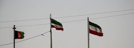 Afganistán y bandera iraní que vuelan adentro en el Islam Quala fotografía de archivo libre de regalías