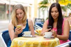 Afgeleide vrienden die telefoons met behulp van bij koffie Stock Foto