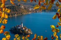 Afgetapt, Slovenië - de Zonsopgang bij meer tapte genomen vanuit Osojnica-gezichtspunt met traditionele Pletna-boot en Afgetapt K Stock Afbeelding