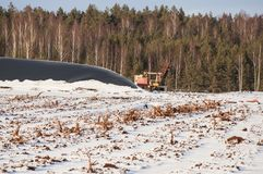 Afgevoerd die turfmoeras met sneeuw en industriële machine in de winter wordt behandeld stock afbeeldingen
