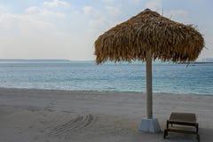 Afgezonderd met stro bedek paraplu op een stil strand stock afbeelding