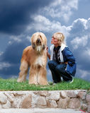 Afghan-dog and woman. Afghan dog and woman on a background of the sky Royalty Free Stock Images