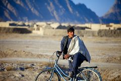 Afghan Kid watch a passing patrol Stock Photography