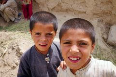 Afghan Kids watch a passing patrol Royalty Free Stock Photography