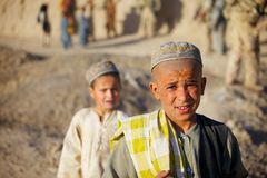 Afghan Kids watch a passing patrol Stock Photography
