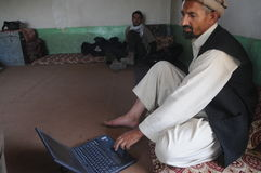 Afghan man working on laptop. Afghan man working on his laptop in Muhammad Agha district, Logar Province, Afghanistan Stock Photo