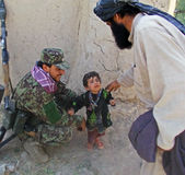 Afghan officer playing with a children in Afghanistan Royalty Free Stock Image