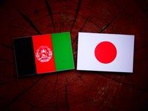 Afghani flagga med den japanska flaggan på en isolerad trädstubbe Fotografering för Bildbyråer