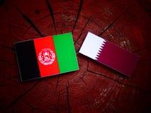 Afghani flagga med den Qatari flaggan på en isolerad trädstubbe Arkivbild