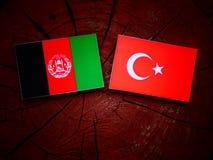 Afghani flagga med den turkiska flaggan på en trädstubbe Arkivbild