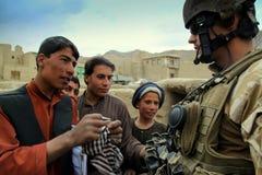 Afghanischer Junge argumentiert mit tschechischem Soldaten Stockfoto
