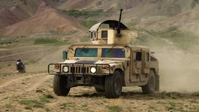 Afghanistan - Circa 2018: Rugged military grade HE High Mobility Multipurpose Wheeled Vehicle HMMWV, Humvee driving. As of 2018, over half of Afghanistan`s stock video footage