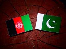 Afghanistan flag with Pakistan flag on a tree stump isolated. Afghanistan flag with Pakistan flag on a tree stump stock illustration