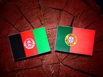 Afghanistan flag with Portuguese flag on a tree stump isolated. Afghanistan flag with Portuguese flag on a tree stump stock illustration